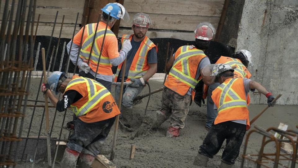 Des ouvriers coulent du ciment sur un chantier.