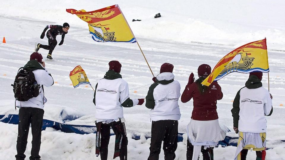 Des gens en bordure de la piste de patinage de vitesse brandissent des drapeaux du Nouveau-Brunswick pour encourager un patineur.