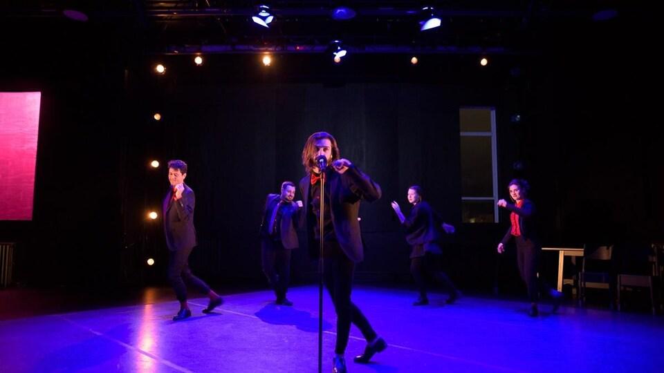 Xavier Gould chantant sur scène avec un pied de micro.