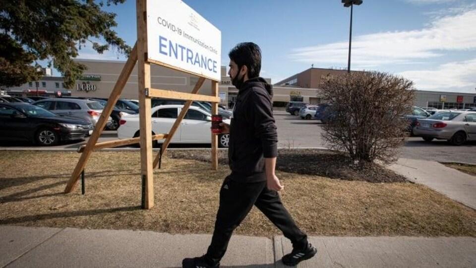 Un homme, tenant un café, marche d'un pas actif sur le trottoir.