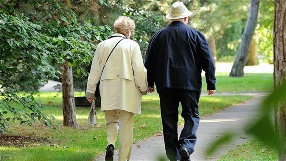 Deux personnes âgées se promènent dans un parc.