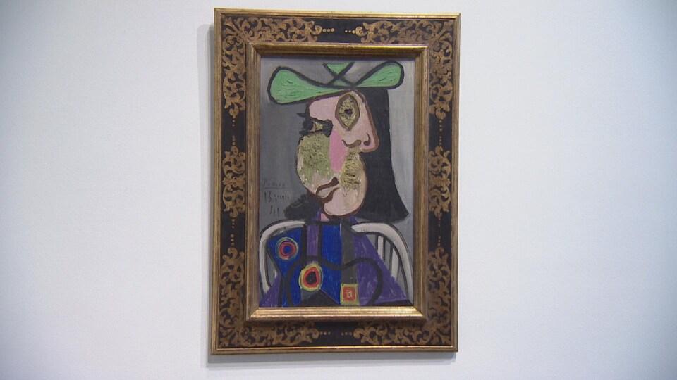 Cadre accroché à un mur présentant un portrait du style cubisme d'une dame assise, portant une robe fleurie et un chapeau vert.