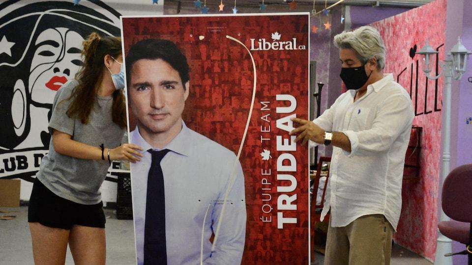Une bénévole et Pablo Rodriguez tiennent une pancarte du premier ministre Justin Trudeau.