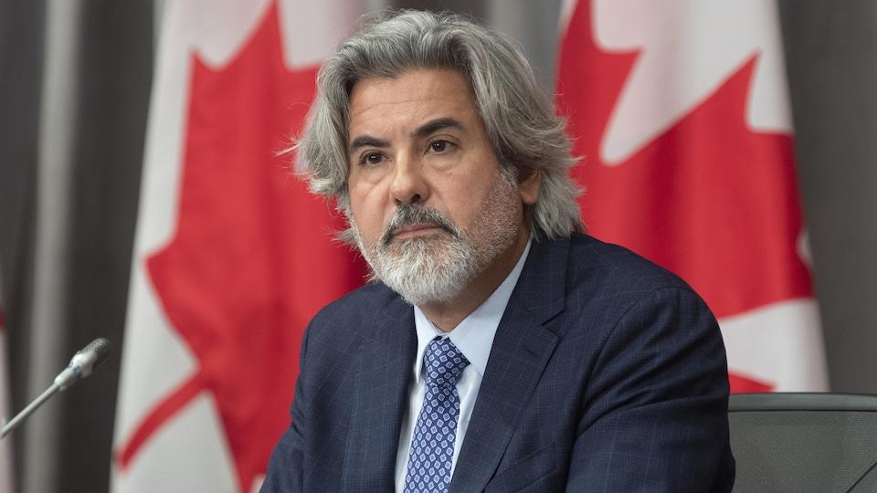Pablo Rodriguez assis devant des drapeaux du Canada.
