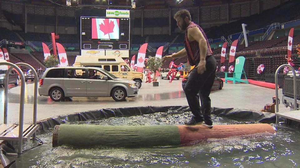 Un bûcheron tente de se tenir debout sur un tronc qui flotte dans l'eau à l'intérieur d'un stade vide.