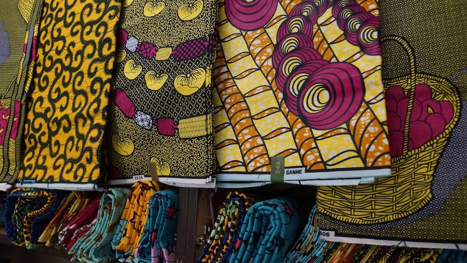 Plusieurs tissus colorés et imprimés disposés côte à côte.