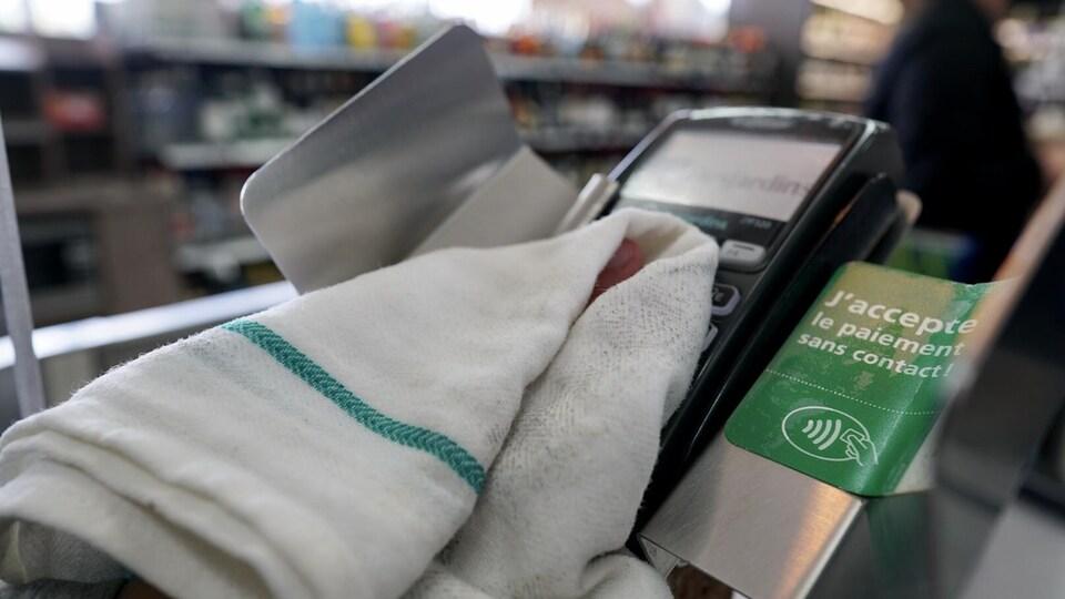 Une main tient un linge et nettoie une machine qui sert à payer avec une carte de crédit ou de débit.