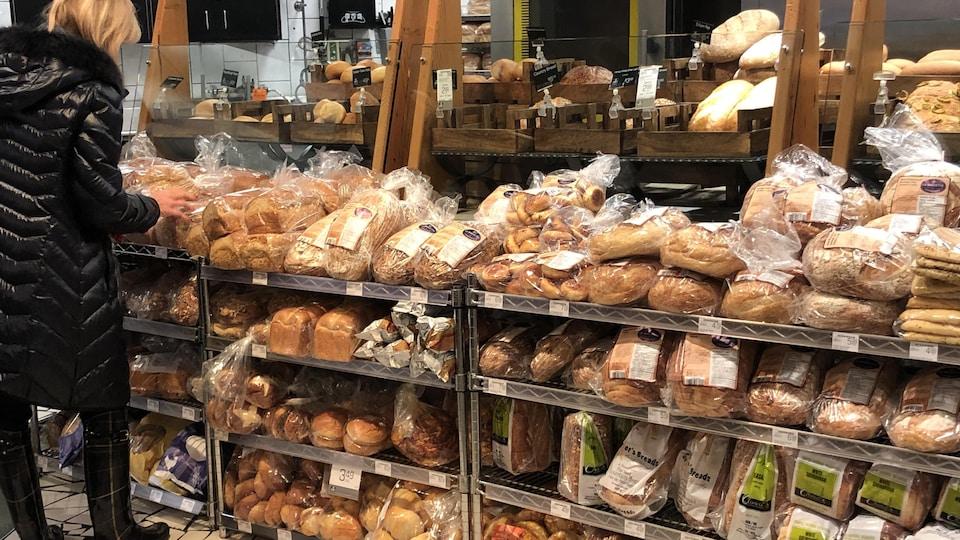 Une dame aux cheveux blonds avec des bottes et un manteau d'hiver noirs regarde un étalage de pains dans un commerce.
