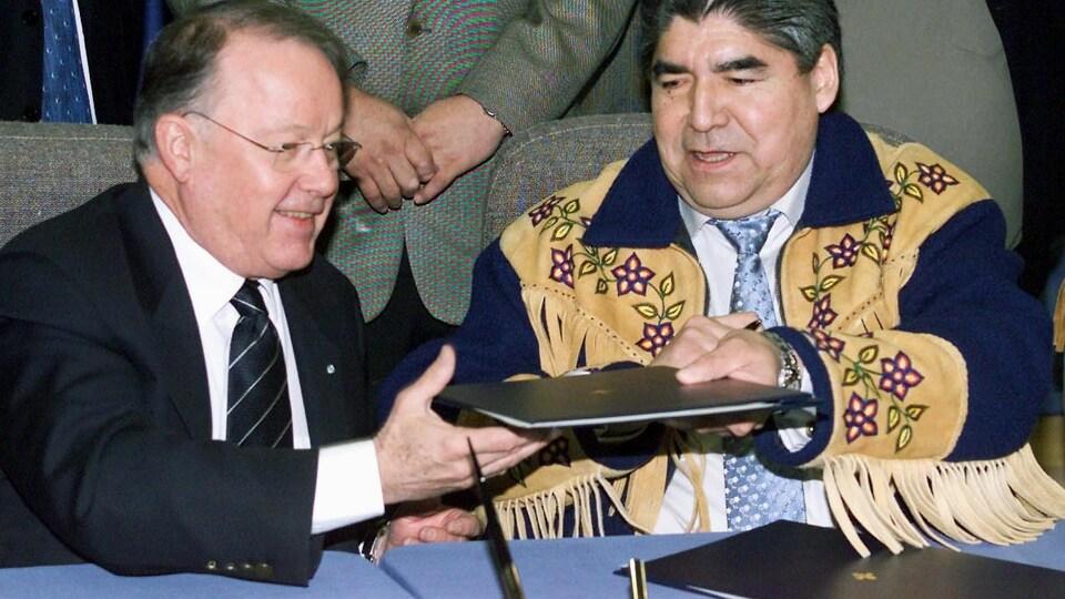 Ted Moses et Bernard Landry sont assis et s'échangent le texte de l'entente pour le signer.