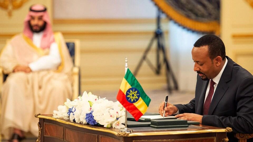Un homme assis, signe un papier. Derrière lui ont aperçoit un haut dignitaire saoudien.