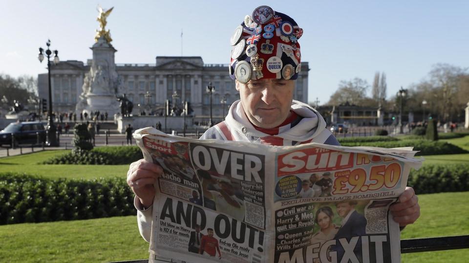 Un homme, debout, dans le parc du palais de Buckingham, arborant une tuque couverte d'épingles associées à la famille royale.