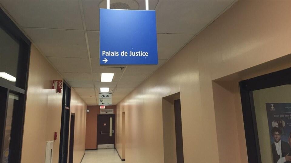 Panneau bleu du gouvernement indiquant le palais de justice à droite.