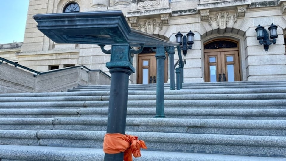Le mémorial pour les Autochtones érigé sur les marches du palais législatif de la Saskatchewan a été vidé. Il ne reste plus qu'un tissu orange accroché à une rampe.