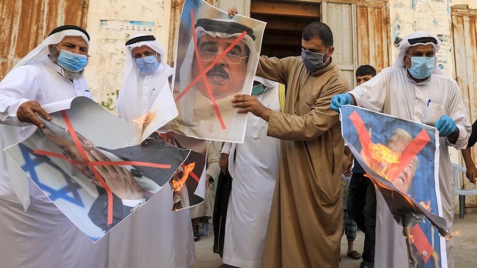 Des hommes avec des masques contre la COVID-19 tiennent des affiches en feu représentant les trois hommes d'État.