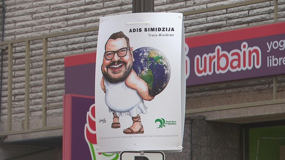 Pancarte du candidat sur un poteau au centre-ville; on y voit une caricature du candidat qui porte la planète Terre sur son dos.