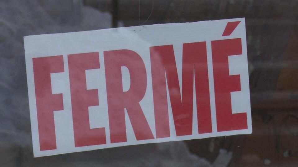 Une pancarte affichant fermé collé sur une vitre.