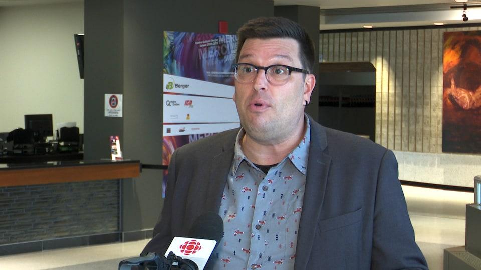 Un homme debout devant un micro de Radio-Canada