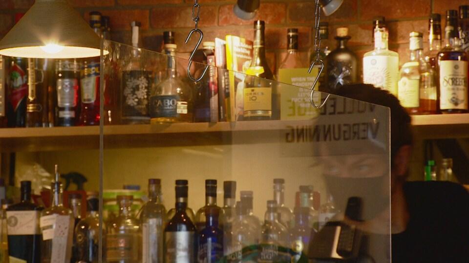 Un barman derrière une séparation en plexiglas dans un bar.