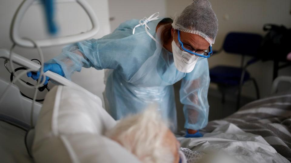 Un médecin se penchant sur le lit d'un patient.