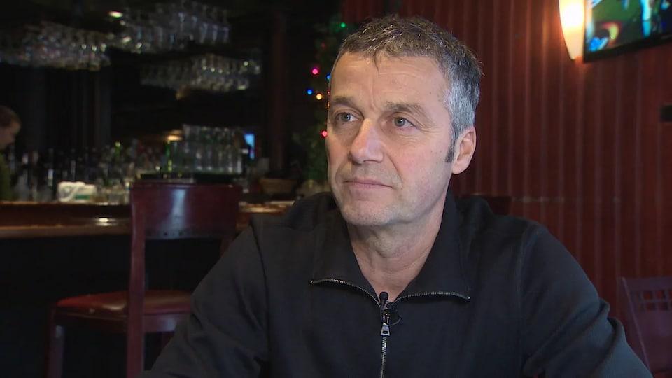 Un homme assis dans un restaurant-bar.