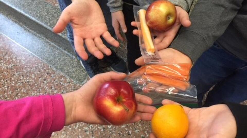 Des mains d'enfants avec des aliments sains.