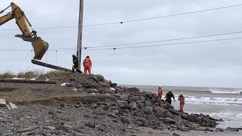 Travailleurs d'Hydro-Québec s'affairent sur la rive.