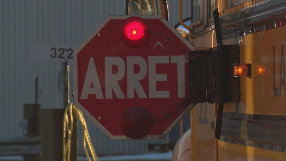 Un panneau d'arrêt déployé sur un autobus scolaire.