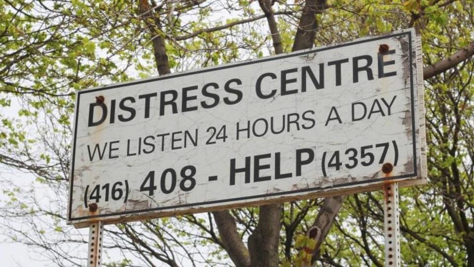 Sur le panneau il est écrit : centre de détresse, nous écoutons 24 h sur 24. Est ensuite écrit le numéro de téléphone où appeler à l'aide.