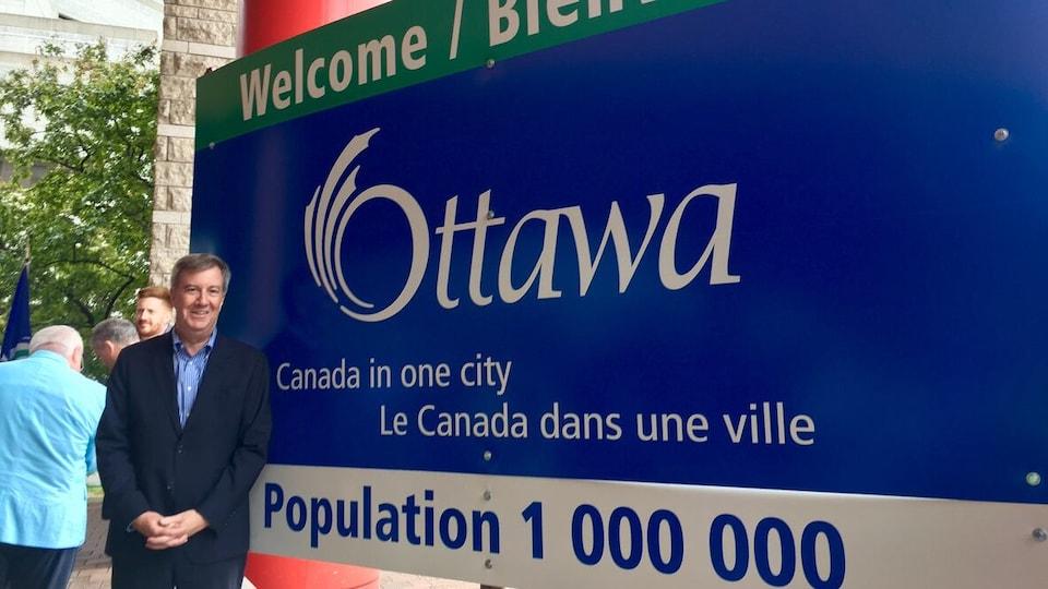 Jim Watson devant un panneau d'accueil de la ville d'Ottawa où la population de 1 million est indiquée et où se trouve le slogan «le Canada dans une ville».