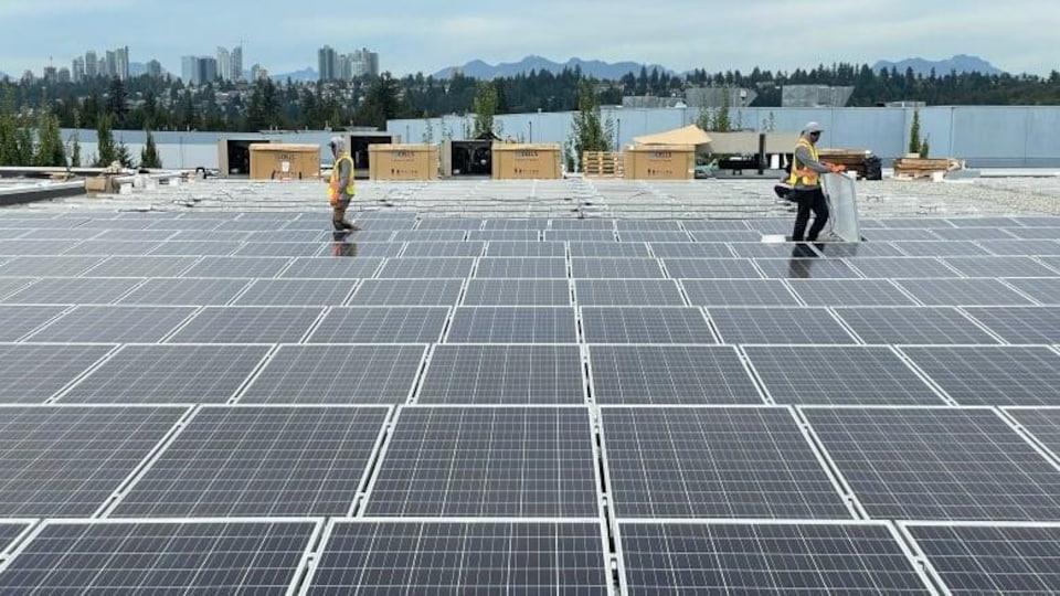 Deux personnes installent des panneaux solaires sur un grand toit plat.