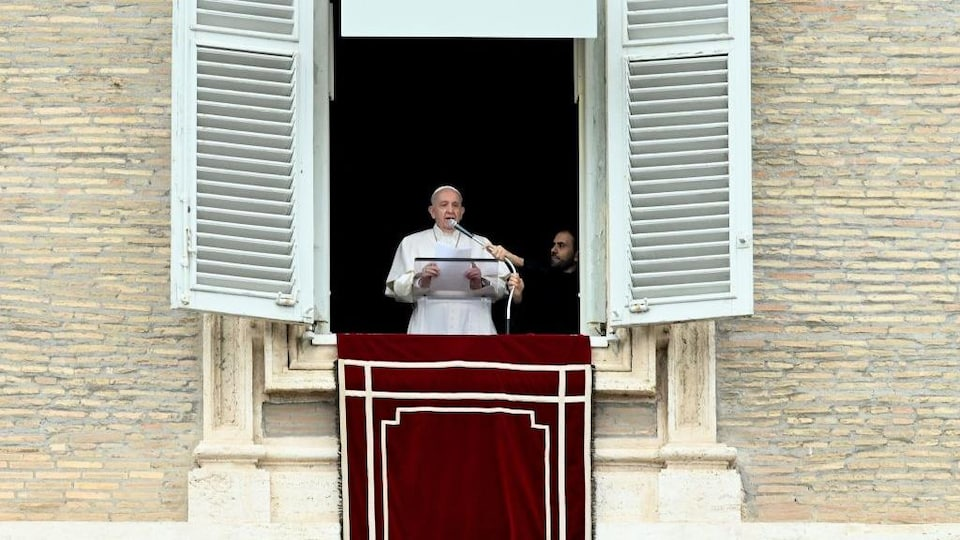 Pope speaks with huge brackets from a window.  A man holds his microphone.