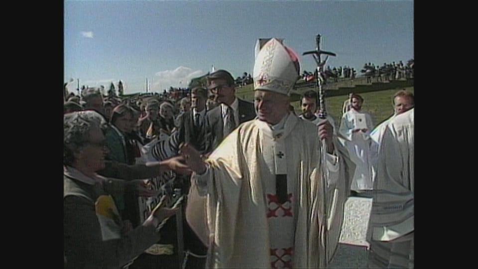 Le pape Jean-Paul II sert la main d'une femme.