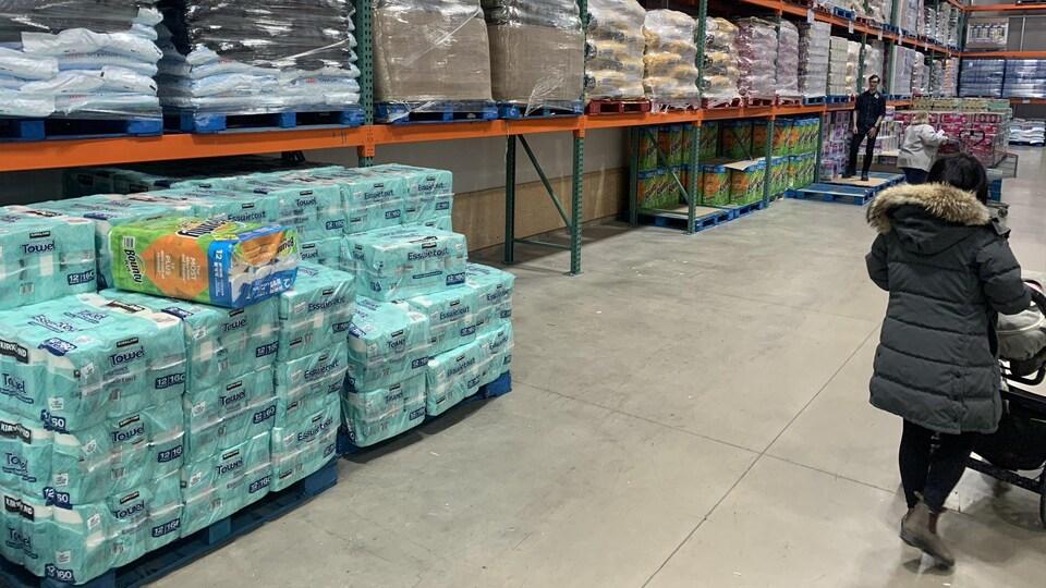 Une cliente passe devant les étagères.