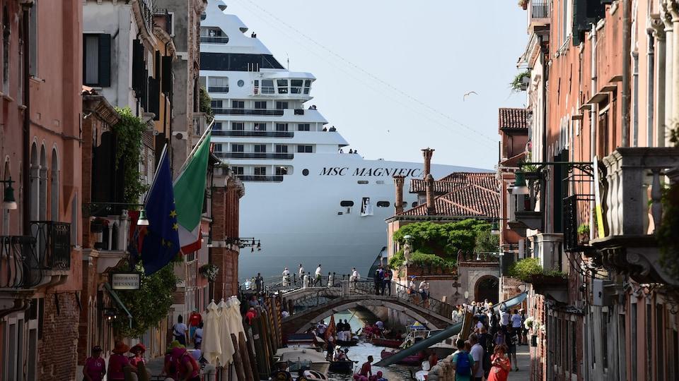 Vue de la proue d'un bateau de croisière au détour d'une rue à Venise.