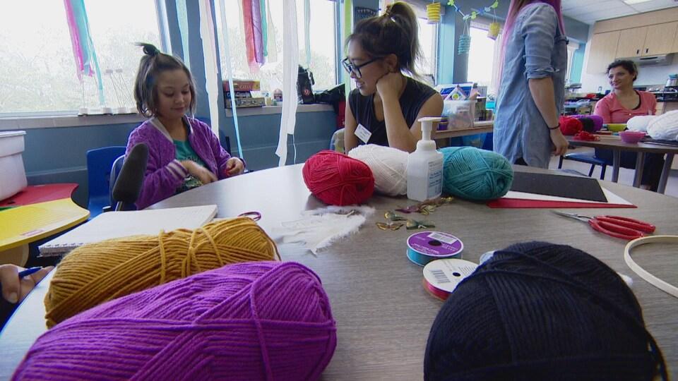 Une fillette et une jeune femme sont assises à une table, sur laquelle sont posées des pelotes de laine, des ciseaux et d'autres accessoires.