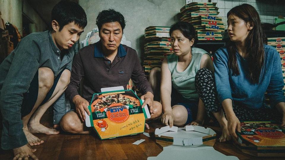 Une famille est assise au sol avec une boîte de pizza devant elle. Il y a plusieurs boîtes de pizza derrière eux.