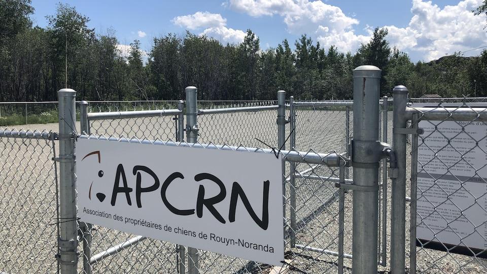Un terrain plat entouré de clôtures, avec une pancarte où il est inscrit : Association des propriétaires de chiens de Rouyn-Noranda.