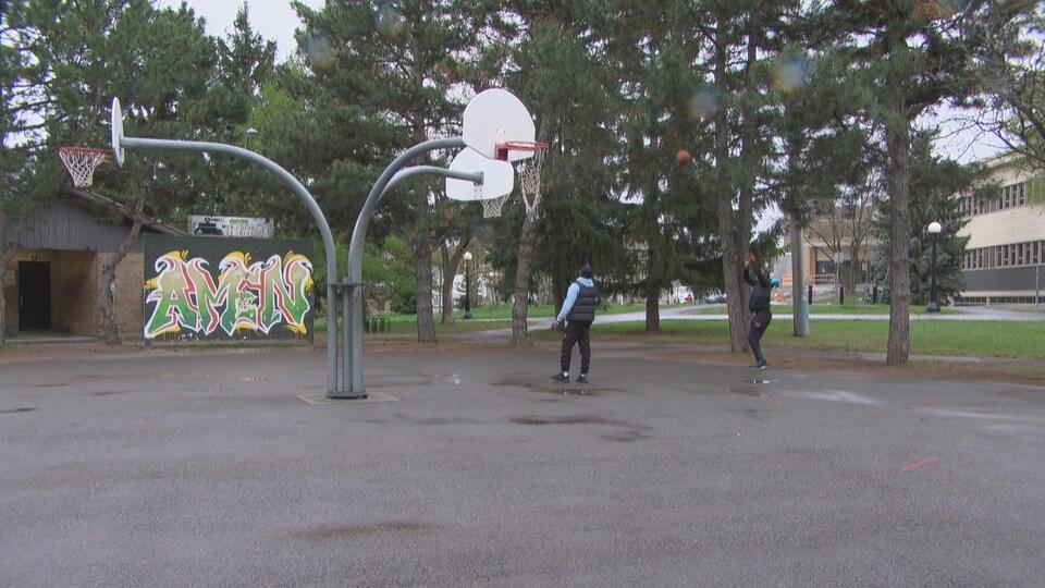 Ibrahima Doumbouya et Ezechiel Nana pratiquent leur lancer sur un terrain de basket extérieur.