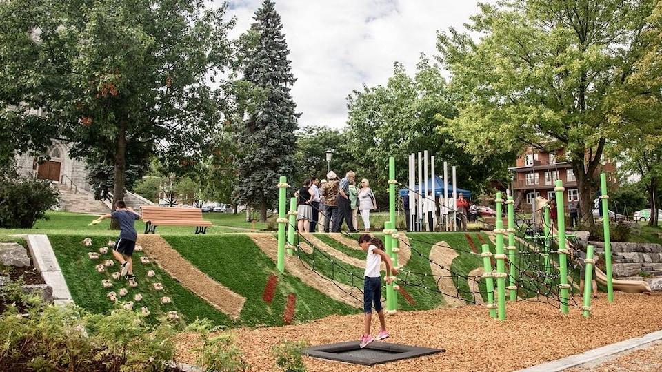 Des jeunes s'amusant dans un parc-école. Une jeune fille saute sur un petit trampoline et un garçon monte sur un mur d'escalade.