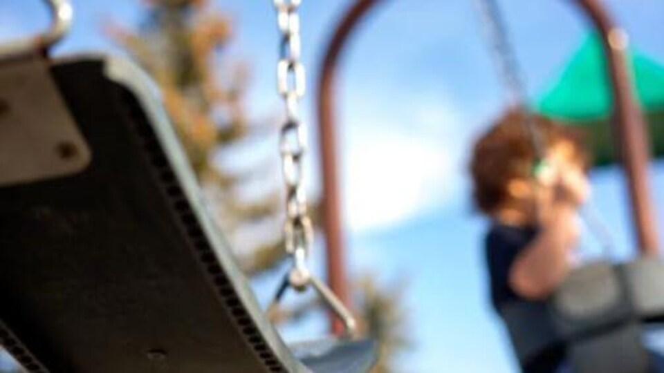 Une balançoire dans un parc, alors qu'un enfant se retrouve sur la structure de jeu. La photo est floue.