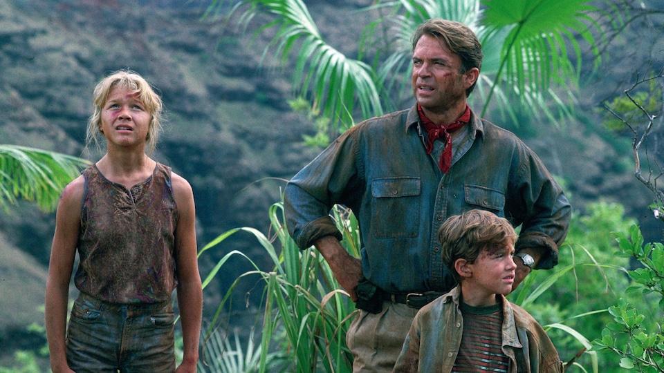 Un homme et deux enfants, une fille et un garçon, sont dans une forêt et portent des habits tachés de terre.