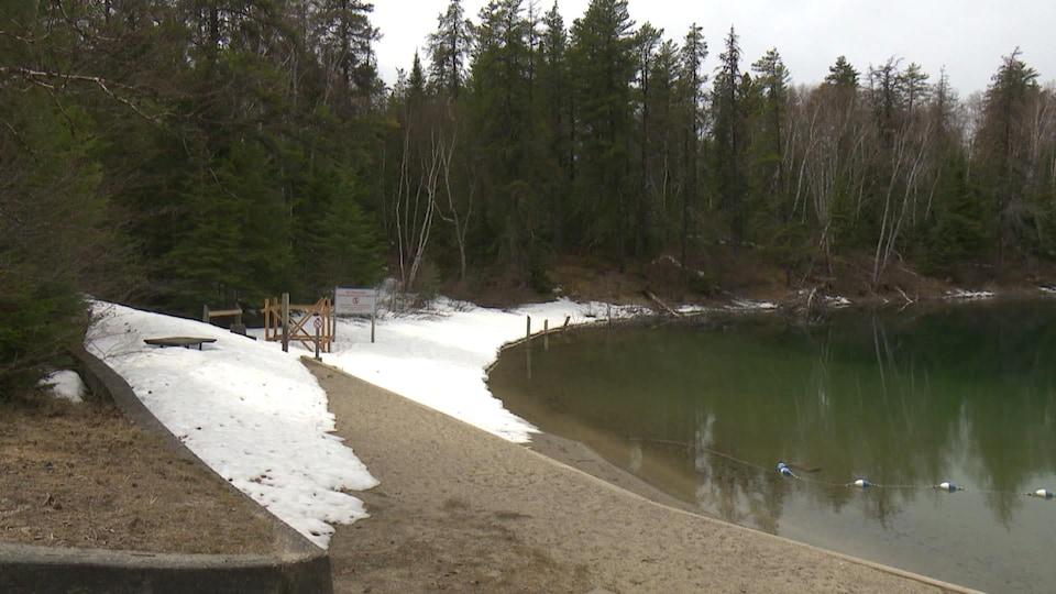 La plage d'un lac est partiellement enneigé.