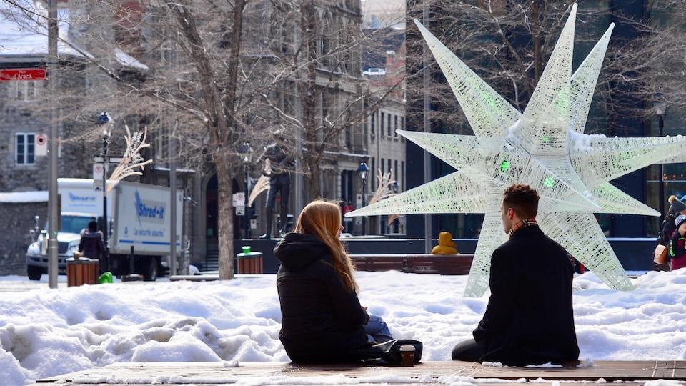 Un homme et une femme sont assis sur le banc d'un parc enneigé.