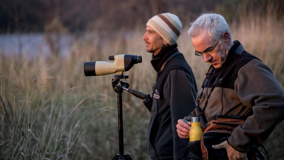 Deux hommes observent les oiseaux à l'aube.