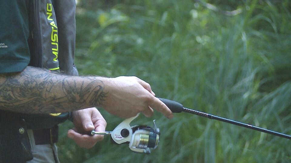 Main d'un employé du parc national tenant une canne à pêche.