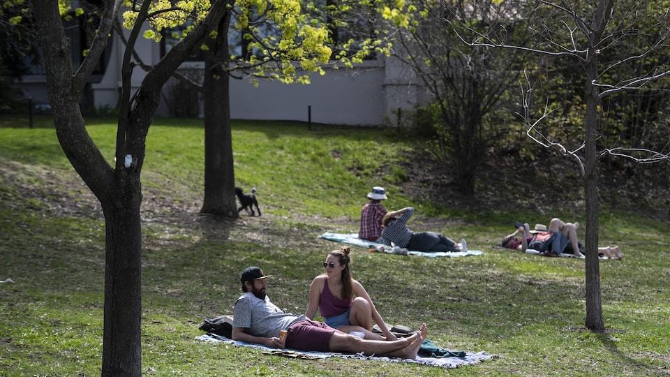 Des gens allongés sur des couvertures sur l'herbe dans un parc.