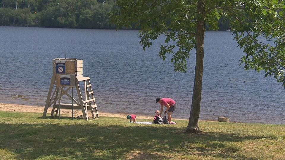 Famille sur le bord de l'eau du lac avec une chaise vide de sauveteur.