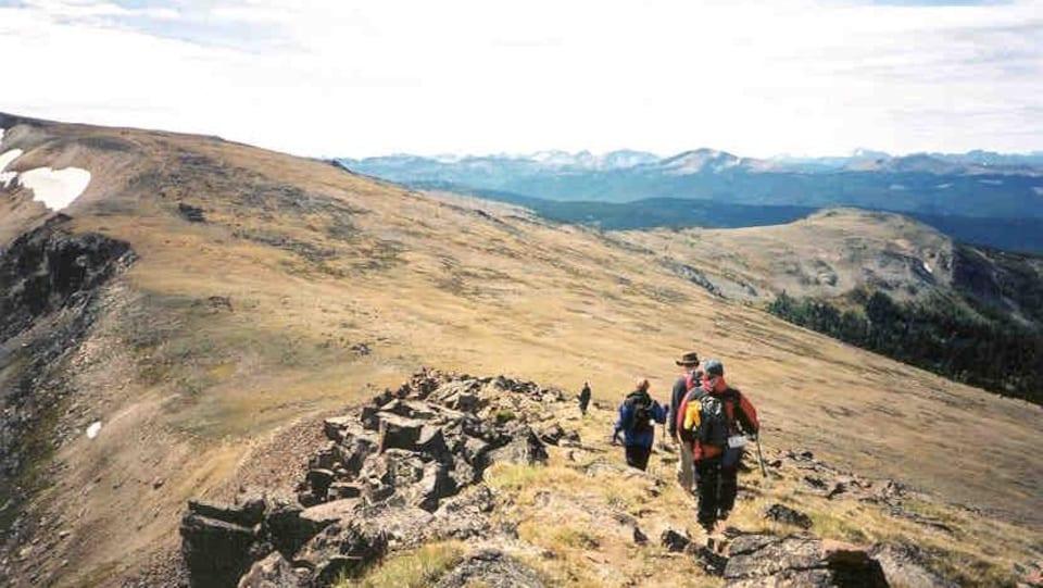 En avant-plan, des randonneurs descendent une piste située sur une crête de montagne. En arrière-plan, des montagnes.
