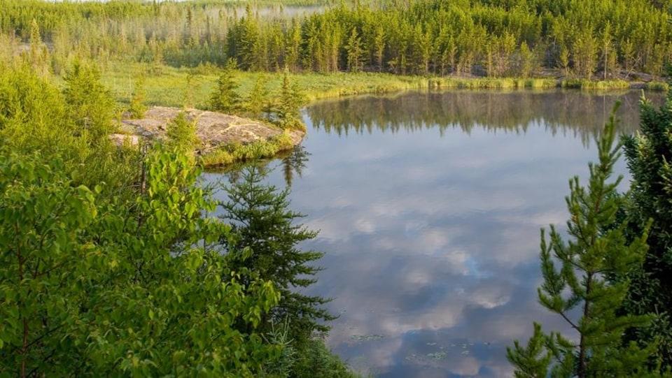 Le ciel bleu et quelques nuages se reflètent dans un petit lac bordé par une forêt de conifères dans le parc provincial de Nopiming, au Manitoba.