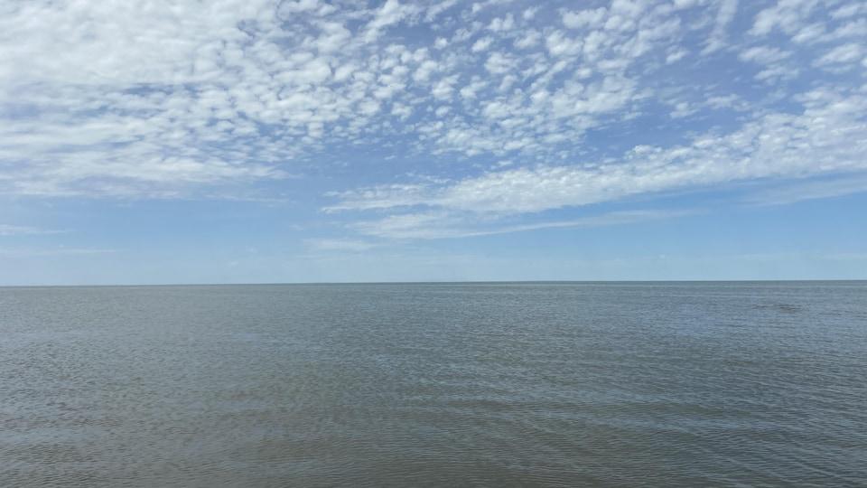 Le vent fait onduler les eaux du lac sous un ciel de nuages cotonneux et épars.